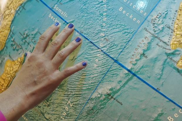 Die Welt in Händen, mit dem Finger auf der Landkarte ... © Copyright by PANORAMO